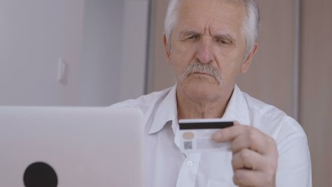 Senior man online shoping at home on laptop, typing credit card number