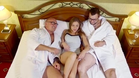 young woman and two adult men are lying together in a big bed in hotel room, unconventional group sex