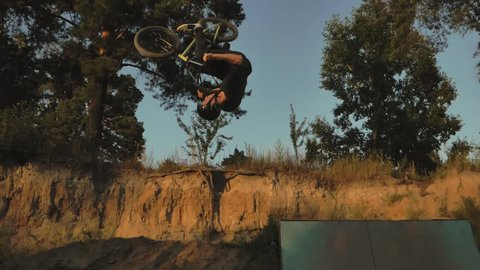 A young man practicing freestyle BMX in BMX park at dusk