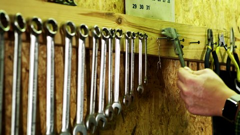 Human hand hangs on wall vernier caliper. Mechanical tools hanging on wall in workshop. Auto repair service interior with instruments. Row of wrenches and measuring tool on wall in vintage garage