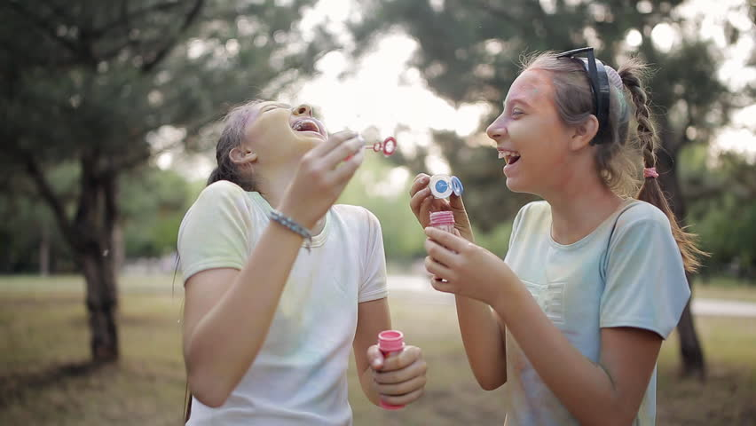 Two girls get dirty with dry colors Holi blow soap bubbles