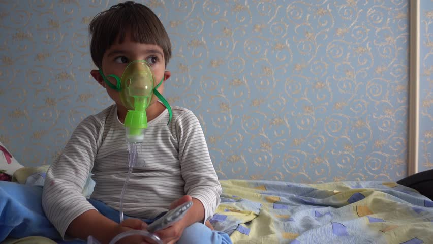 4K Sick child with nebuliser mask and TV remote control in his hands  | Shutterstock HD Video #1015491820