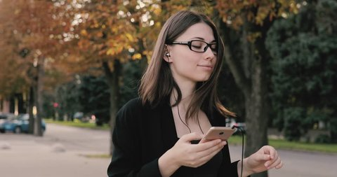 Woman listening to music or audiobook while walk in autumn city