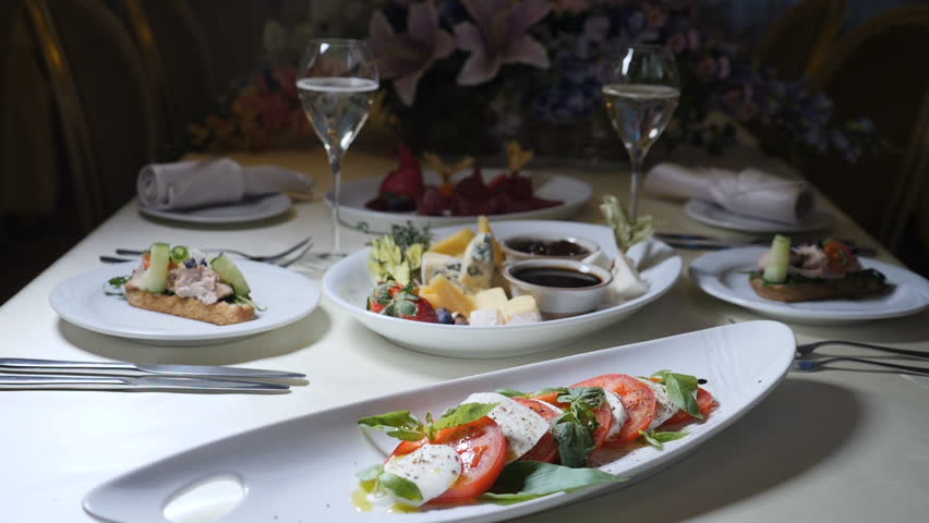 Food art. Chef in restaurant pours wine vinegar onto Caprese salad in slow motion. Cool cooking. Restaurant table serving.