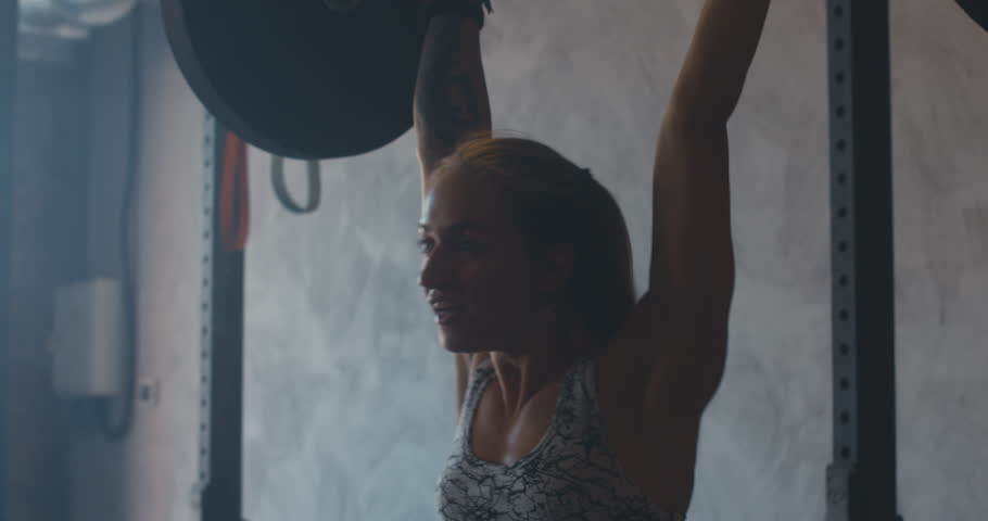 HANDHELD portrait of young fit Caucasian female athlete working out with a barbell in a functional gym. 4K UHD | Shutterstock HD Video #1015501000