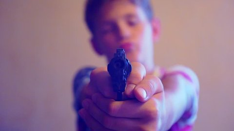 blurred silhouette of a boy, who directs the gun at the camera.shallow depth of field