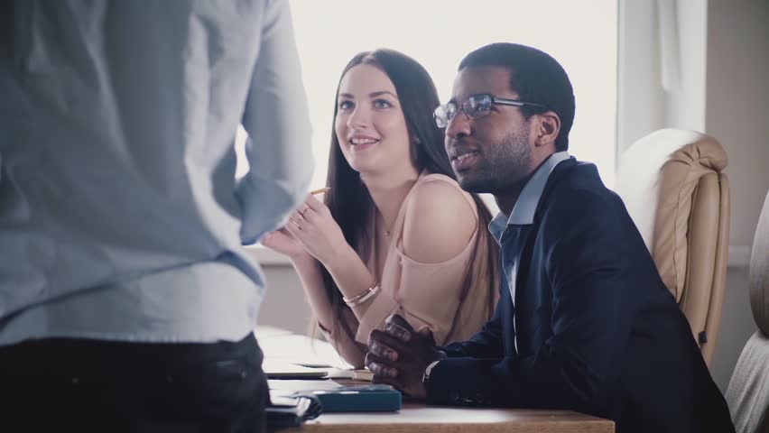 Happy multiethnic team listening to unrecognizable male executive, smiling at office meeting slow motion close-up. | Shutterstock HD Video #1015530760