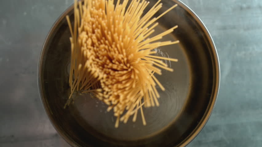 Throwing spaghetti pasta into water. Overhead shot. Shot with high speed camera, 4K. Slow Motion.