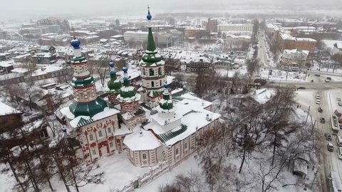 Beautiful winter flight above old Russian city Siberia. Church of the exaltation of the Holy cross of the God Irkutsk. Tourist religion attraction. Snow roofs  old wooden houses. Aerial drone 4k