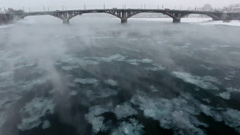 Unique abstract flight above Angara river Irkutsk city. Center main arc bridge day car road traffic. Extreme cold winter snow blizzard weather. Iceberg flow from Baikal Aerial drone cinematic