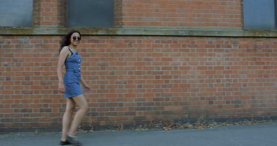 A Pretty Mix Race Young Girl Exploring The British Streets On a Summers Day.Wearing a Blue Denim Summer Dress With Trendy Sunglasses. Walking In front Of a Brick Wall. Having Fun On A Summers Day. #1015553590