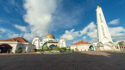 Beautiful Time lapse of blue sky and scattered clouds at Straits of Malacca Mosque in Melaka, Malaysia at daylight. Motion timelapse pan up. Full HD 1080p.