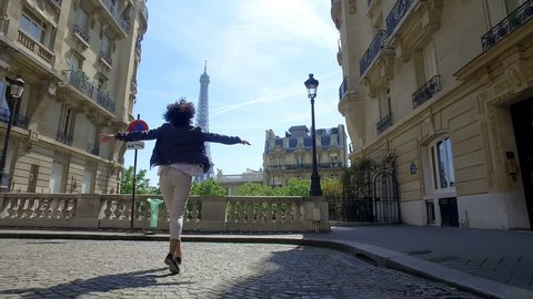 Happy woman enjoy panoramic view of Paris Eiffel Tower walking and jumping on traditional street pavement and old buildings facades