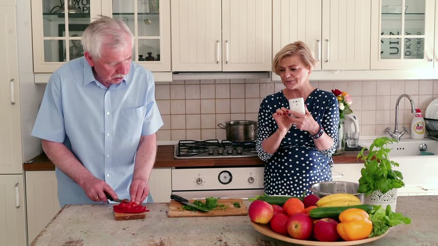Senior man cutting peiper and make excuse his wife browsing smartphone  | Shutterstock HD Video #1015589590