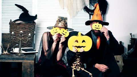 Halloween party and celebration concept. Wizard, witch and the little skeleton hide their faces behind pumpkins. Family in costumes have fun on halloween