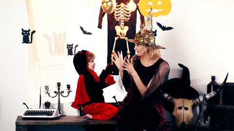 The boy in the dragon suit and a women in witch suit is playing against the background of a halloween. Halloween celebration concept