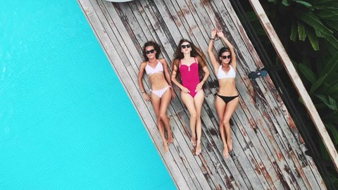 AERIAL. Camera zooming out. Top view of three young woman in sun glasses, lying near pool at luxury jungle villa. Three friends relaxing at the swimming pool.