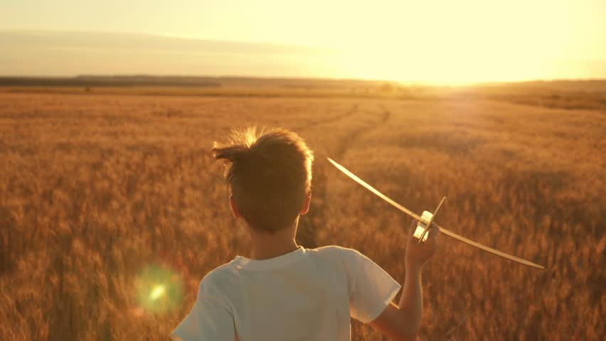 Happy child runs with a toy airplane on a sunset background over a field. The concept of a happy family. Childhood dreams | Shutterstock HD Video #1015632130