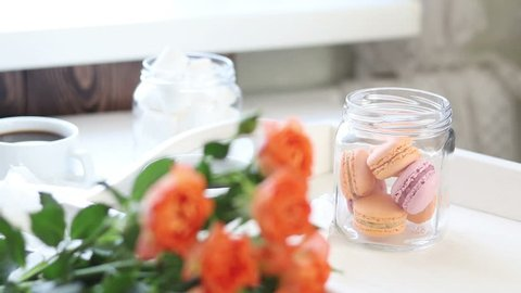 Cup of coffee. Orange mango and citrus macarons and marshmallow in jars. Fresh little roses. Light wooden background, sunlight.