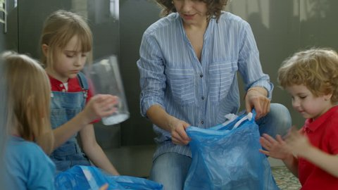 Tilt up shot of mother and three children of elementary school age sitting on floor in kitchen and talking while putting litter in blue plastic bags