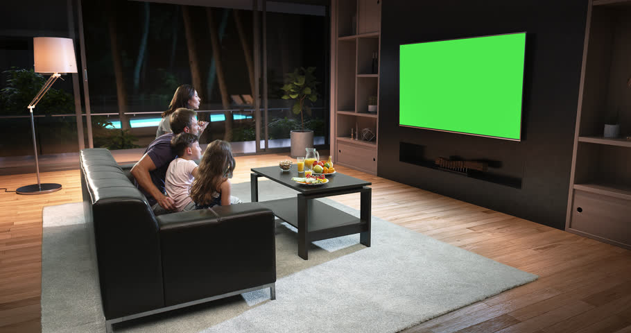 A family is watching a TV and celebrating some joyful moment, sitting on the couch in the living room. The living room is made in 3D. TV is green screen for further editing.