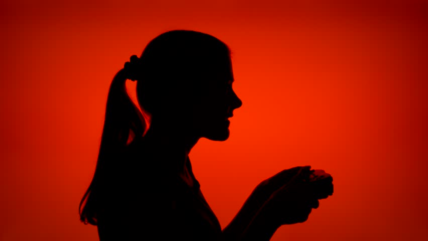 Silhouette of young woman gamer playing video game online. Female's face in profile with game console on red background. Black contour shadow of teenager's half-face winning computer game