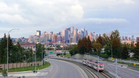 View of Downtown Calgary showing traffic and commuter train at sunset in Calgary, Alberta, Canada.