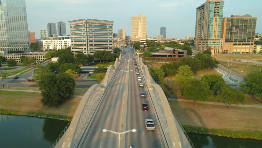 FORT WORTH, TEXAS, USA - AUGUST 1, 2018:  Aerial video of classic cars driving into Downtown Fort Worth Texas for a car show