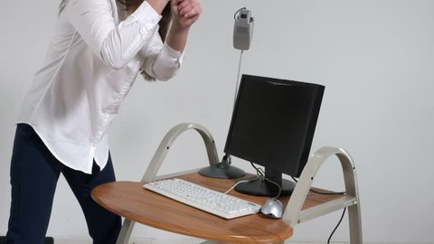 Crazy woman office worker destroying computer with sledge hammer