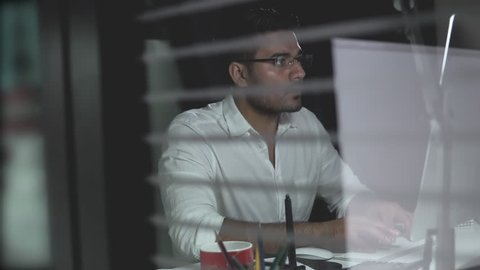 Asian businessman staying overtime late at night working in the office, hidden camera behind glass partition
