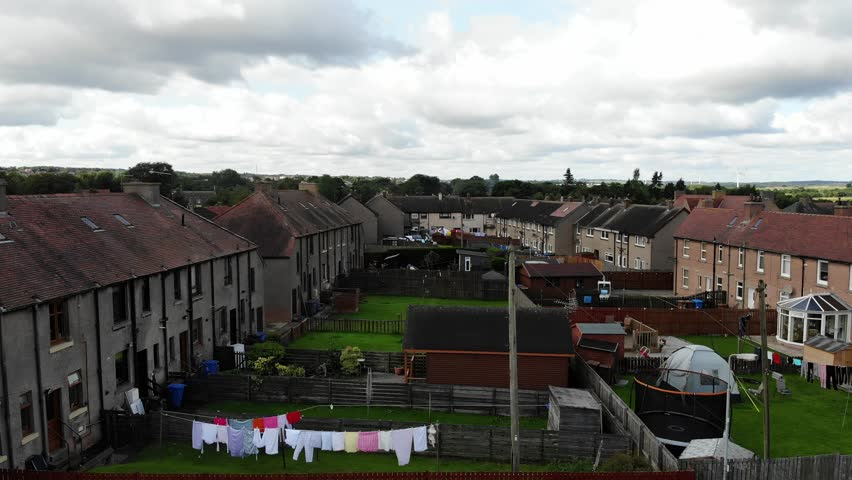 Aerial drone footage of suburban houses, road and fields in Edinburgh, Scotland, UK