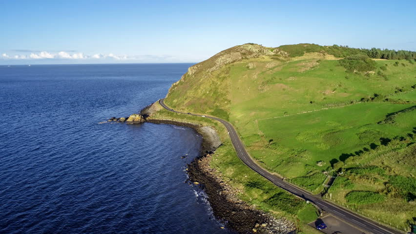 Northern Ireland, UK. Causeway Coastal Route a.k.a Antrim Coast Road near Ballygalley Head and resort. One of the most scenic coastal roads in Europe. Aerial 4K video | Shutterstock HD Video #1015708060