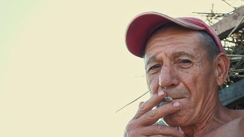 Portrait of a smoking hard worker against the background of a rural scene. A farmer in a cap smokes a cigarette