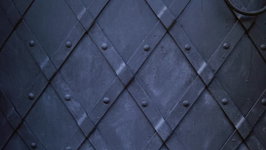 An old medieval restored black metal door reinforced with overlaid plates. Move the camera from bottom to top.