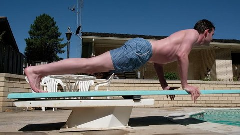 Strong and healthy young white man doing push ups on a diving board in a backyard in his swimming suit. Working out by the pool. Exercise to build upper body strength. Doing push ups outside by a pool
