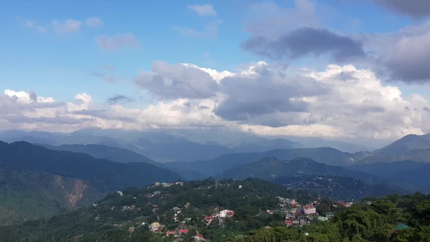 A pan of a village in the mountains. The shot features thick clouds and a feeling of breeze. Shot in Baguio, Philippines.