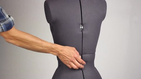 hand of tailor like a plastic surgeon gently change waist size and width of the back on a female sewing mannequin, tightening the adjusting screw, gray background
