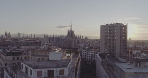 Aerial drone footage view of sunrise of famous statue on cathedral Duomo in Milan Italy  // no video editing