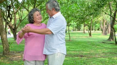 Sweet senior couple dancing in park. Old asian man and woman dancing together in park standing up. Senior lifestyle concept.