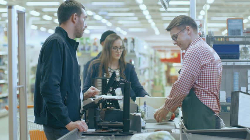 At the Supermarket: Checkout Counter Professional Cashier Scans Groceries and Food Items. Clean Modern Shopping Mall. Shot on RED EPIC-W 8K Helium Cinema Camera. | Shutterstock HD Video #1015777330