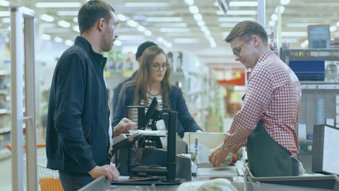 At the Supermarket: Checkout Counter Professional Cashier Scans Groceries and Food Items. Clean Modern Shopping Mall. Shot on RED EPIC-W 8K Helium Cinema Camera.