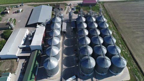 Aerial view. Large modern grain complex among the vast southern fields. Storage of cereal crops in huge gray metal tanks on a modern current. Agricultural scenery with silos at low altitude.