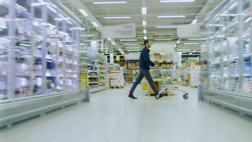 At the Supermarket: Man in a Hurry Pushes Shopping Cart full of Items, He's Walking Through Different Section of the Big Bright Mall. Following / Moving Side view Footage. Shot on RED EPIC-W 8K.