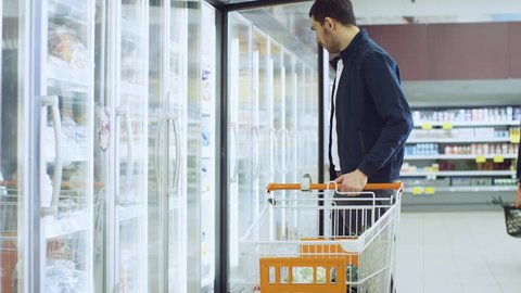 At the Supermarket: Handsome Man Opens Freezer Door and Puts Frozen Vegetables into His Shopping Cart. Customer Browsing Through Frozen Goods Section of the Store. Shot on RED EPIC-W 8K Helium Camera.