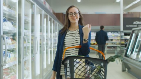 At the Supermarket: Beautiful Young Woman with the Shopping Basket Dances Through Frozen Goods and Dairy Products Section of the Store. Shot on RED EPIC-W 8K Helium Cinema Camera.