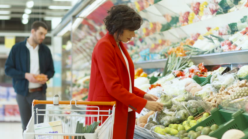At the Supermarket: Beautiful Young Woman Walks Through Fresh Produce Section, Chooses Vegetables and Places them in Her Shopping Cart. Shot on RED EPIC-W 8K Helium Cinema Camera.
