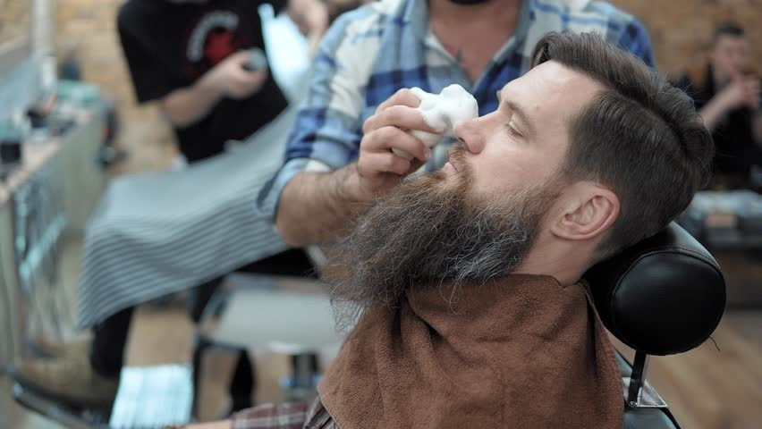 Barber shaves men with a long beard with straight razor blade in s hair salon or barbershop. Man's haircut and shaving at the hairdresser, barber shop and shaving salon.