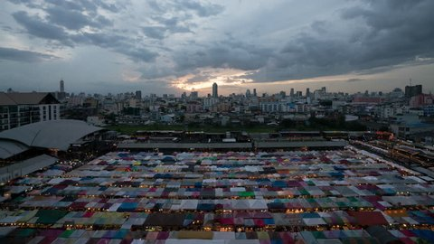 4k timelapse day to night Aerial view of Bangkok night market in Bangkok city downtown with sunset sky and clouds at Bangkok , Thailand. And colourful tents