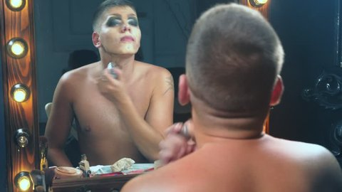 travesty-diva. The concept of a transvestite. Man-actor turns into a woman. a man applies a make-up on his face. in the room in front of the mirror. 4k, slow motion, shooting steadicam