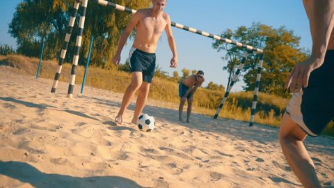 Soccer players in dynamic action funny play on the sand in beach football in summer sunny day under sunlight.